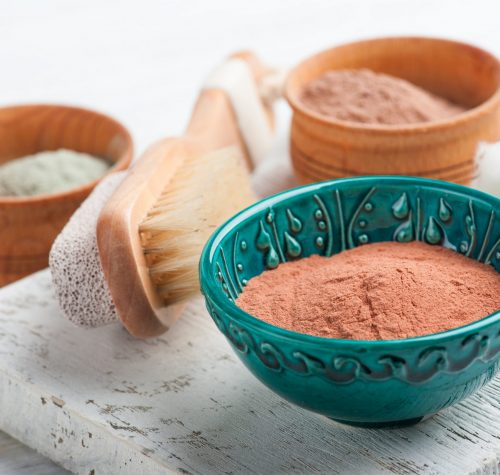 Red and blue cosmetic moroccan clay powder, spa composition with brush on white background