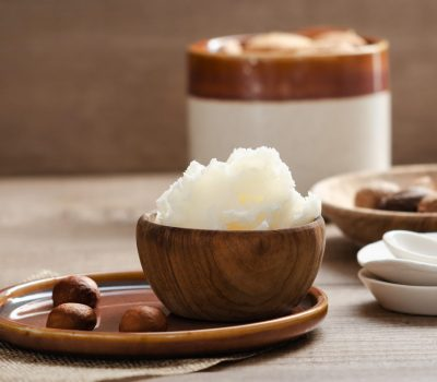 Shea butter in wooden bowl with nuts . Free text space.