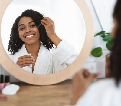 Skin nutrition. Beautiful black woman applying organic moisturizing serum on face with pipette, making beauty treatment at home, reflecting in mirror